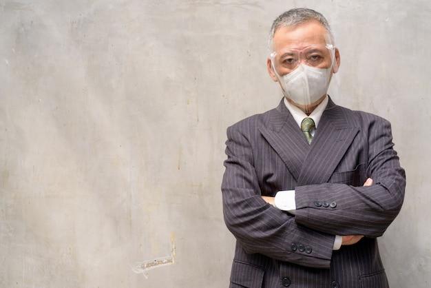 マスクと顔のシールド交差腕を持つ成熟した日本のビジネスマン
