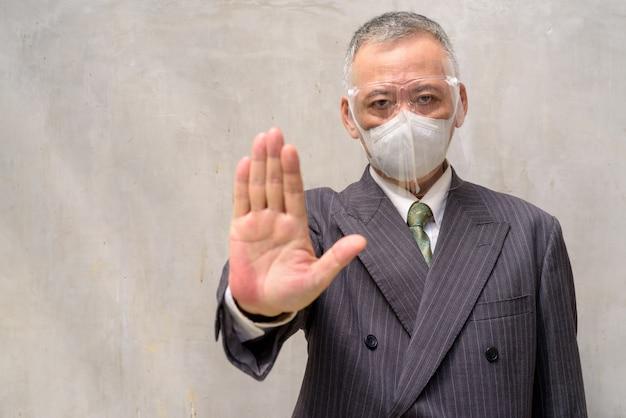 停止ジェスチャーを示すマスクと顔のシールドを持つ成熟した日本のビジネスマン