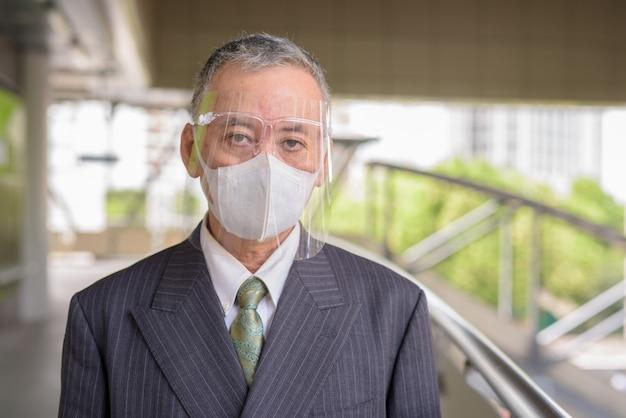 歩道橋でマスクと顔のシールドを持つ成熟した日本のビジネスマン