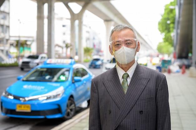 タクシーの駅でマスクと顔のシールドを持つ成熟した日本のビジネスマン