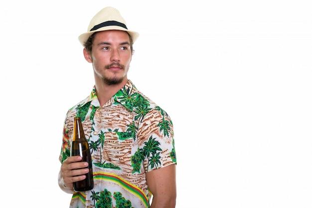 ビールのボトルを押しながら考えて若いハンサムな観光男