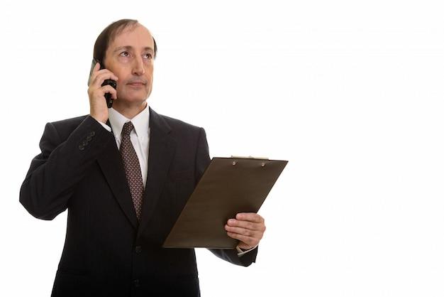 Вдумчивый зрелый бизнесмен разговаривает по мобильному телефону