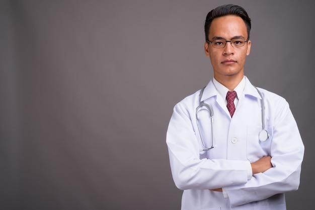 Молодой красивый индийский мужчина доктор против серой стены