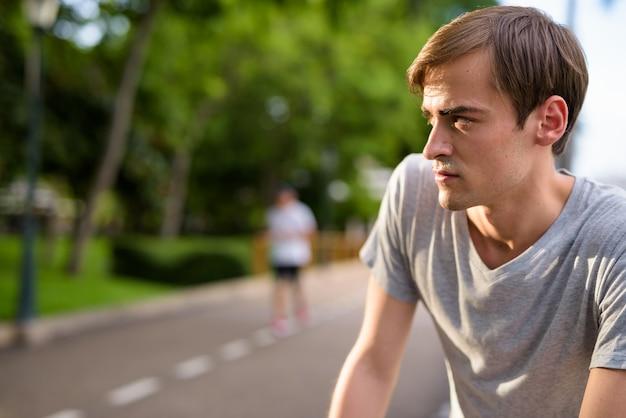 公園でリラックスした若いハンサムな男