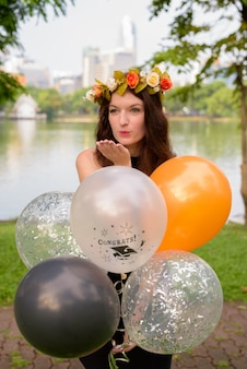 公園で卒業を祝っている若い美しい女性