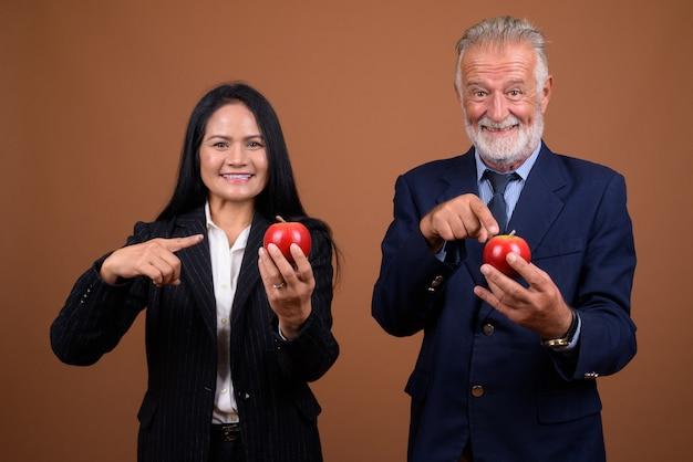 茶色の成熟した多民族のビジネスカップル