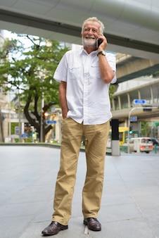 タイのバンコク市を探索するハンサムなシニア観光男