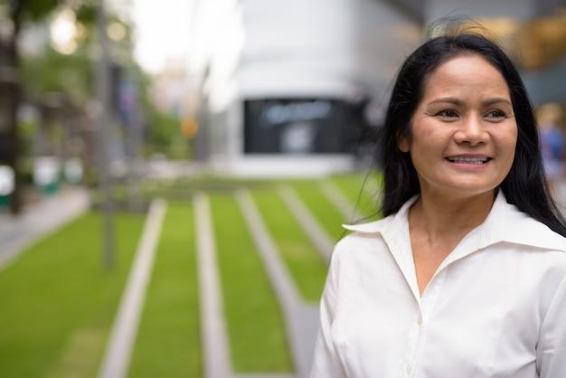Зрелая красивая азиатская коммерсантка исследуя город бангкок