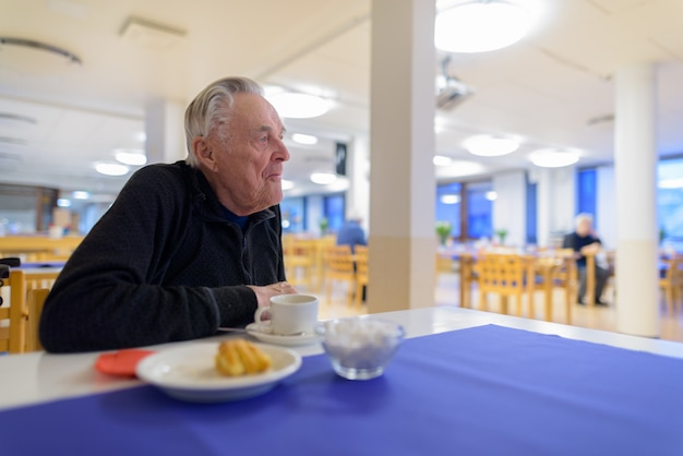 特別養護老人ホームの食堂で食べる年配の男性