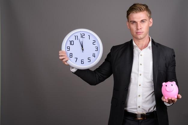 Молодой красивый бизнесмен с костюмом светлых волос нося на серой стене