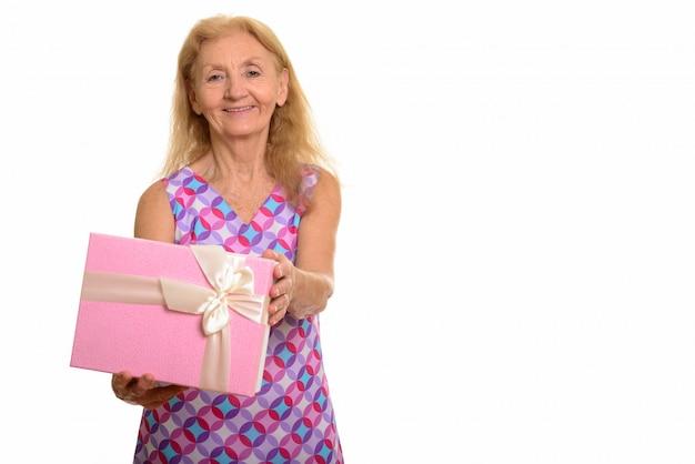 Счастливая старшая женщина усмехаясь и давая подарочную коробку