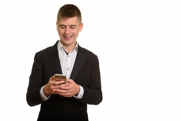 笑顔で携帯電話を使用して幸せな青年実業家のスタジオ撮影