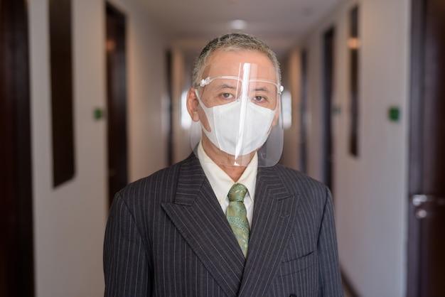 廊下でマスクと顔のシールドを持つ成熟した日本のビジネスマン