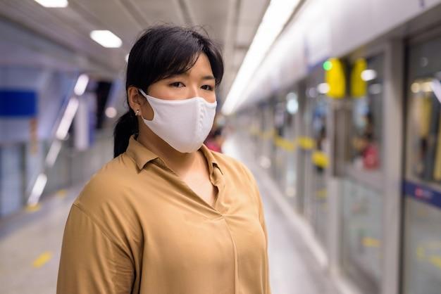 Полная азиатская женщина с маской для защиты от вспышки вируса короны на станции метро