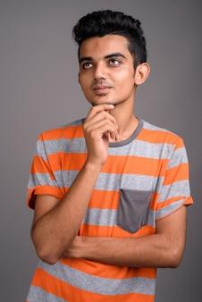 灰色の壁に対して若いインド人