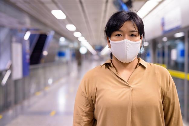 Избыточный вес азиатки с маской для защиты от вспышки вируса короны на станции метро