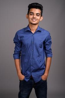 灰色の壁に対して若いインドのビジネスマン