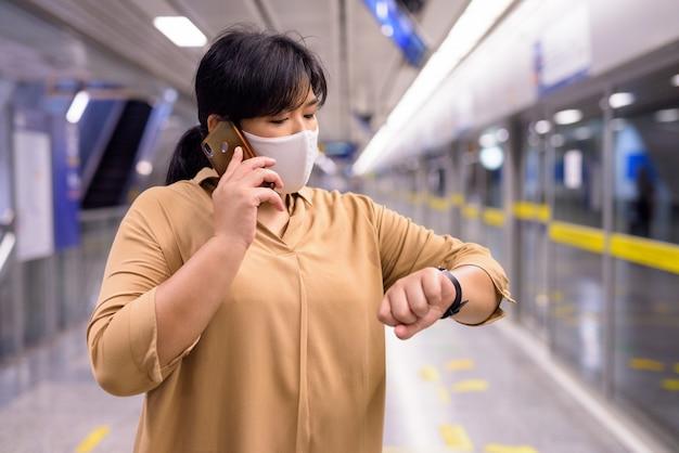 Полная азиатская женщина с маской разговаривает по телефону и проверяет время на станции метро
