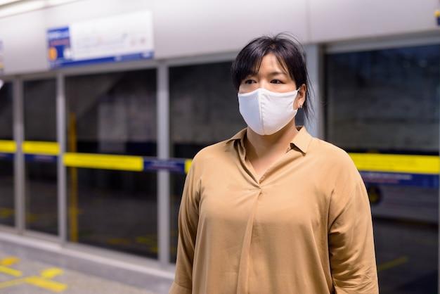 Полная азиатская женщина думает с маской для защиты от вспышки вируса короны на станции метро