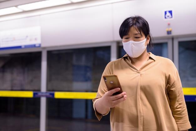 Азиатская женщина с избыточным весом использует телефон с маской для защиты от вспышки вируса короны на станции метро