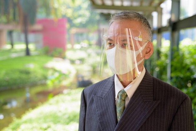 公園でマスクと顔のシールドを考えて成熟した日本のビジネスマン