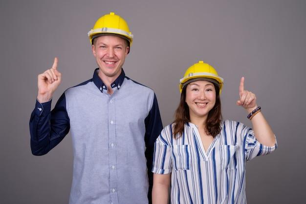 若いハンサムなビジネスマンおよびヘルメットを身に着けている成熟したアジア女性実業家