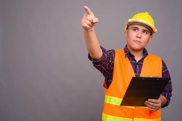 灰色の壁に対して若い男性の建設労働者