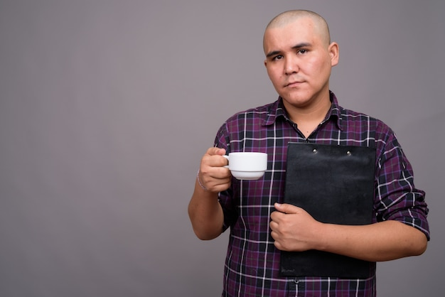 灰色の壁に市松模様のシャツを着ている若いハゲアジア系のビジネスマン