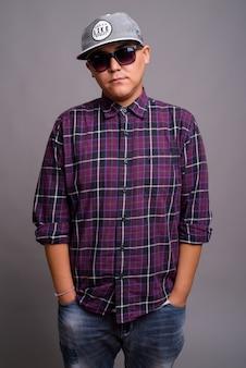 灰色の壁に帽子とサングラスを身に着けている若いアジアのギャングの男