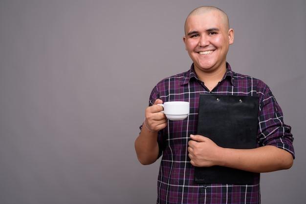 Молодой лысый азиатский бизнесмен в клетчатой рубашке на серой стене