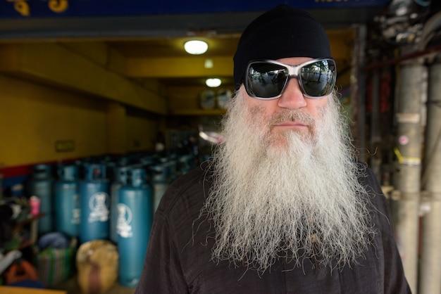 Зрелый бородатый мятежный человек с очками перед бензобаков на открытом воздухе
