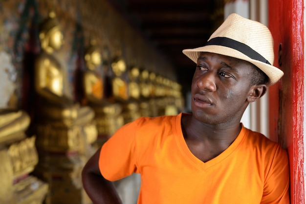ワットアルン寺院の整列した仏の構造のビューに対して考える若い観光客男