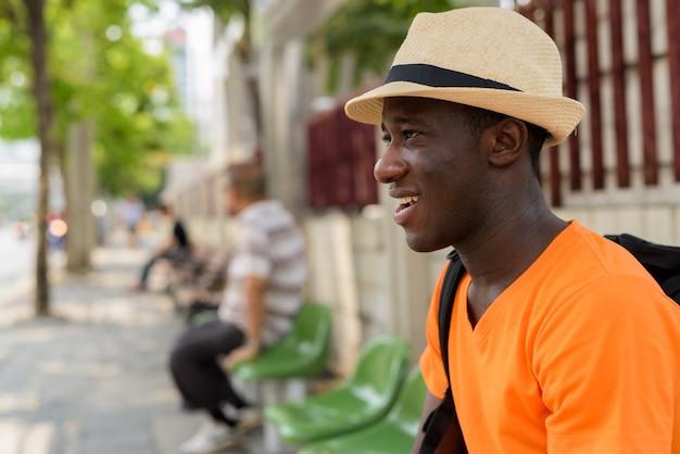 Закройте вверх по взгляду профиля молодого счастливого туристского человека усмехаясь и думая пока ждущ в автобусной остановке бангкока таиланда