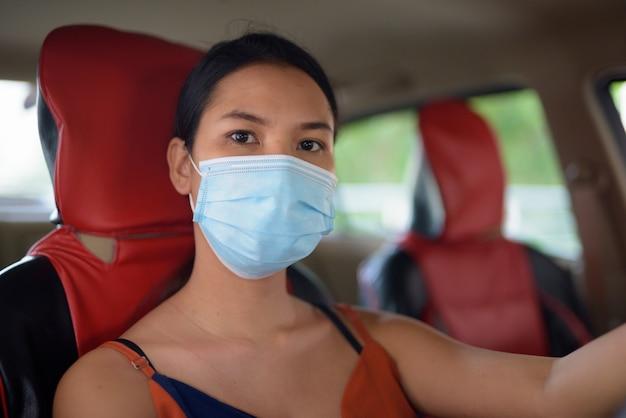 車を運転中にコロナウイルスの発生から保護するためのマスクを持つ若いアジア女性