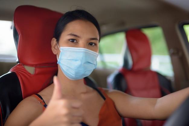 車の中で親指をあきらめるコロナウイルスの発生からの保護のためのマスクを持つ若いアジア女性