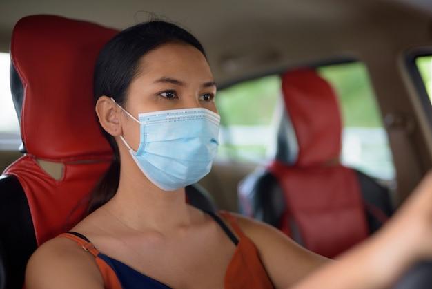 車を運転中にコロナウイルスの発生からの保護のためのマスクを着ている若いアジア女性