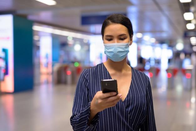 Молодая азиатская коммерсантка с маской используя телефон на станции метро