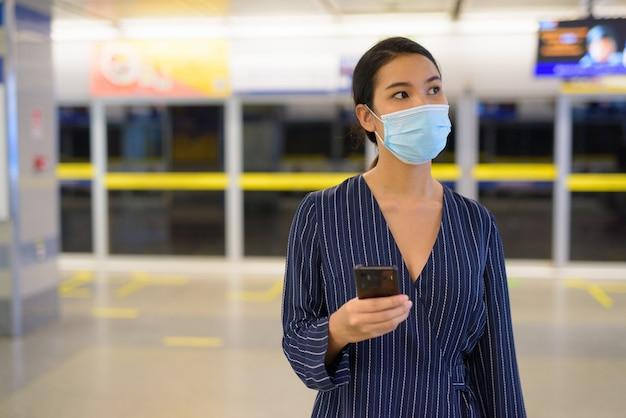 Молодая азиатская коммерсантка с маской думая пока использующ телефон на станции метро
