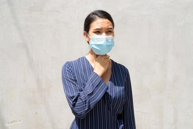 喉の痛みを持つコロナウイルスの発生からの保護のためのマスクで若いアジア女性実業家を強調