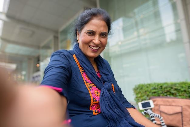 Портрет зрелой красивой индийской женщины, исследующей город бангкок, таиланд