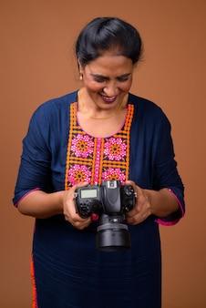 Зрелая красивая индийская женщина против коричневой стены