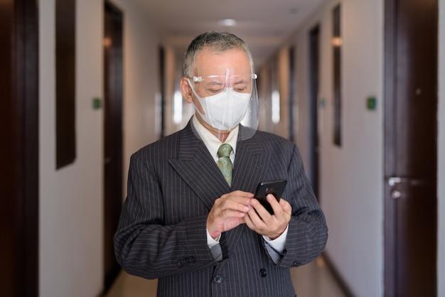廊下で電話を使用してマスクと顔のシールドを持つ成熟した日本のビジネスマン