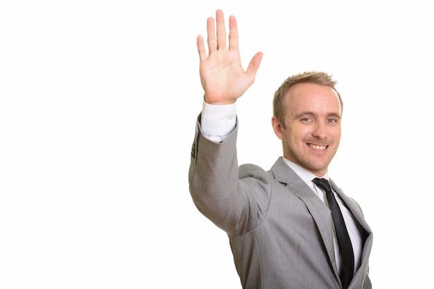 白い壁に対して分離された手を上げる幸せなハンサムなビジネスマン