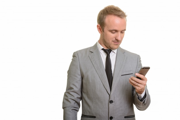 Красивый бизнесмен держа мобильный телефон изолированный против белой стены