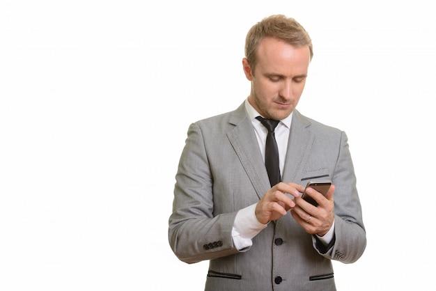 Красивый бизнесмен используя мобильный телефон изолированный против белой стены