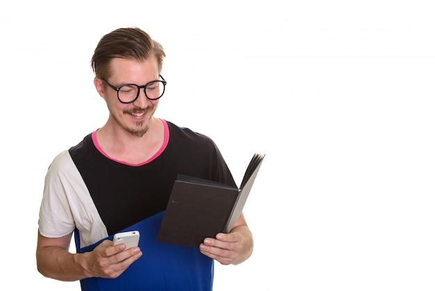 携帯電話を押しながら本を読んで幸せな若者