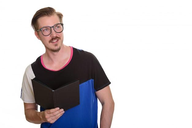 考えながら本を持っている若い幸せな男