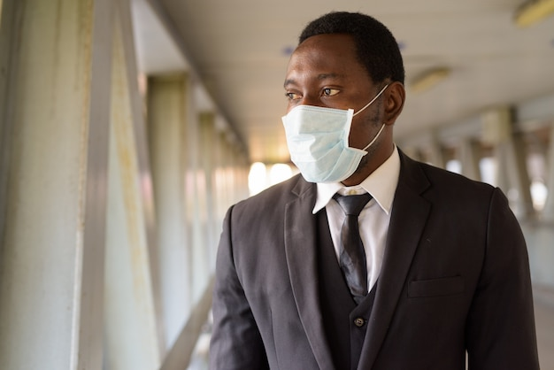 Портрет африканского бизнесмена с маской, глядя на вид на город на пешеходном мосту