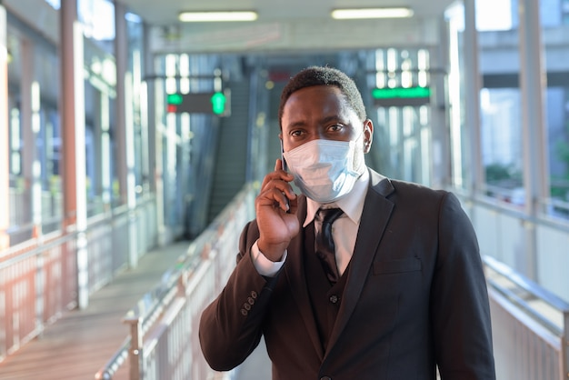 Портрет африканского бизнесмена с маской, разговаривает по телефону на вокзале на открытом воздухе
