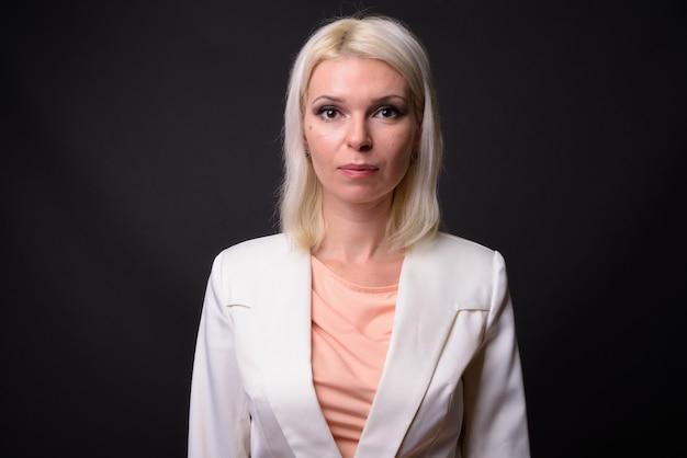 灰色の背景のブロンドの髪と美しい女性実業家